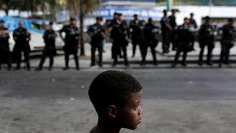 Na Rocinha, menino observa movimentação de policiais; a explosão da violência no Rio se expressa também na vulnerabilidade das crianças a ela