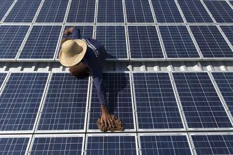 Homem limpa painés solares na comunidade Vila Nova do Amaná, Amazonas 22/09/2015 REUTERS/Bruno Kelly