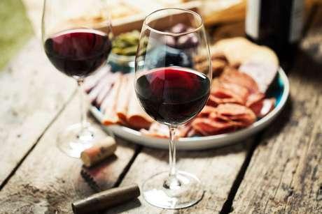 Duas taças de vinho tinto e um prato com frios