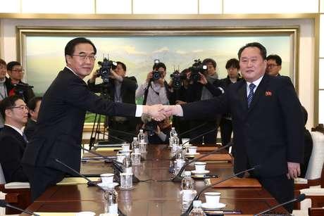 Representantes da Coreia do Sul e Coreia do Norte apertam as mãos durante reunião sobre os Jogos de Inverno