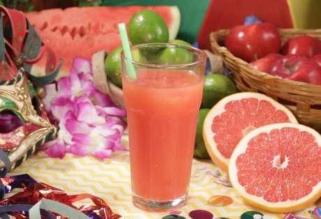 Drink levanta ressaca em uma mesa com frutas e decoração de Carnaval