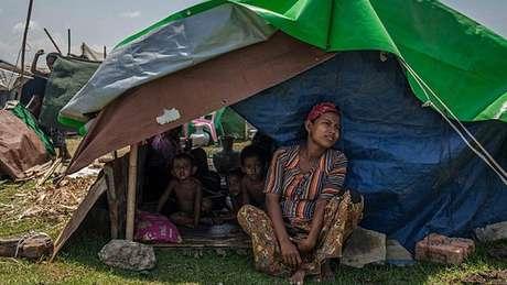 Mulher rohingya senta ao lado dos filhos em abrigo temporário