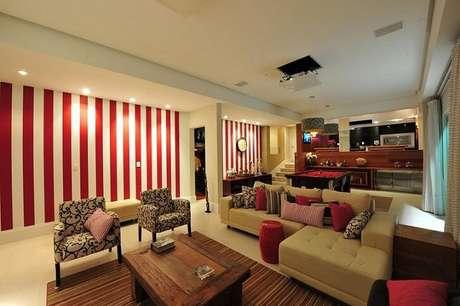23. No projeto de Anna e Anderson, o papel de parede para sala em vermelho e branco combina com os detalhes da decoração