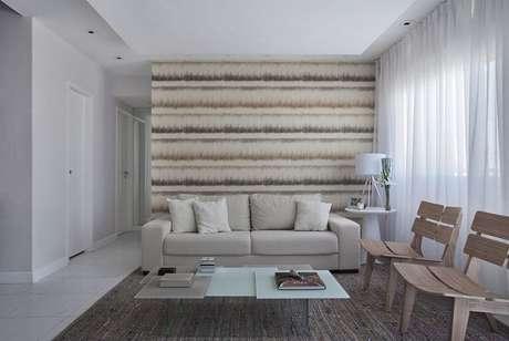 4. Este papel de parede para sala tem linhas horizontais e, por ter um padrão diferente, dá movimento ao cômodo. Projeto de Mariana Martini