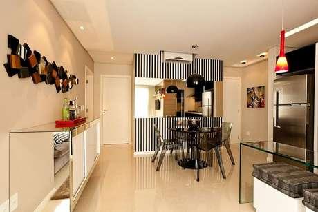 34. Sala de jantar com papel de parede para sala listrado apenas em uma parede. Projeto de Juliana Pippi