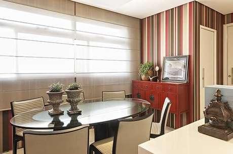 38. Visão mais ampla da sala de jantar com papel de parede para sala listrado seguindo a paleta do ambiente. Projeto de Glaucia Britto