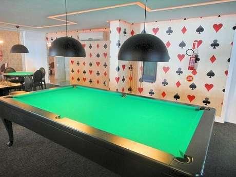 8. Esta sala de jogos, de Gabriela Herde, conta com um papel de parede para sala com estampa de naipes de baralho