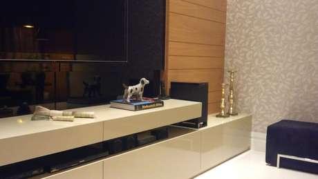 44. Sala de TV com papel de parede de folhagens em tons neutros. Projeto de CS Projetos