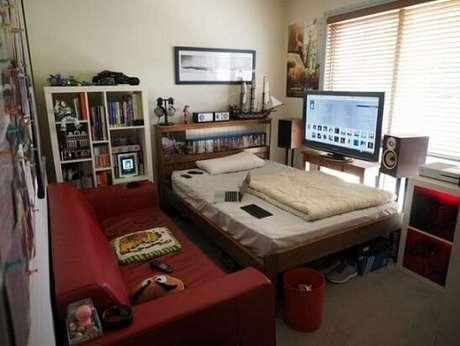 17. Quarto gamer pequeno com games acima da cama e TV em frente ao sofá