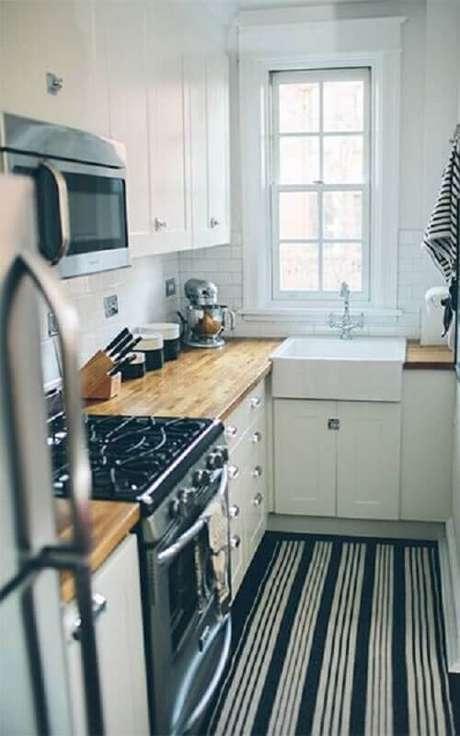 39. O tapete com listras podem dar a impressão de uma cozinha pequena maior visualmente