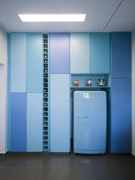 10. Uma decoração de cozinha planeja bem diferente, toda em azul e com adega na vertical.