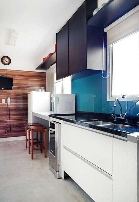 32. Móveis em azul, preto, branco e uma parede de madeira fizeram a cozinha planejada ficar ainda mais bonita