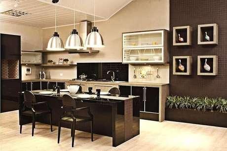 7. Decoração de cozinha bem espaçosa em tons de preto e com pêndulos.