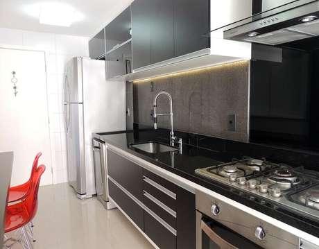 58. Cozinha decorada em tons escuros e com detalhes em aço inox