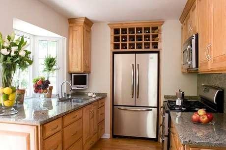49. Uma cozinha muito linda de madeira, com adega e bancada de mármore