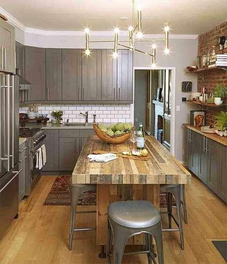 54. A mesa de madeira foi responsável por trazer mais conforto a cozinha decorada com armários de aço inox
