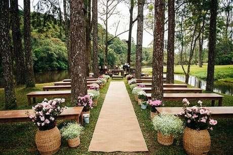 3. A decoração de casamento ao ar livre rústica e com flores ao longo da nave fica linda e romântica