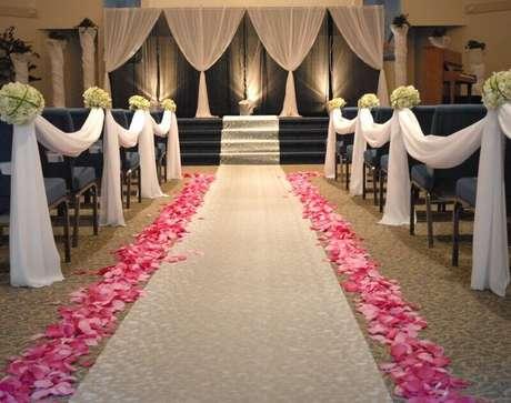 46. As pétalas de rosas ao longo da nave podem deixar a decoração de casamento simples mais romântica