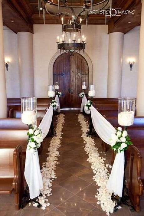 47. O mix de velas e flores deixou a decoração de igreja para casamento super charmosa e delicada