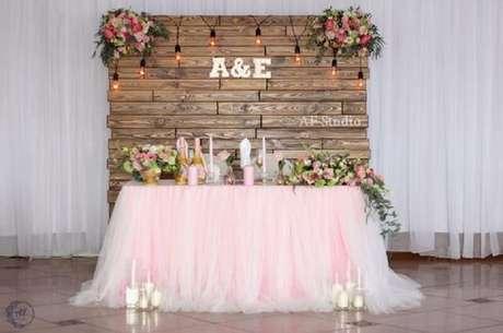 27. O painel de madeira com flores fez um mix de decoração de casamento rústico e romântico.
