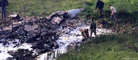 Militares observam destroços de aeronave israelense que caiu neste sábado.