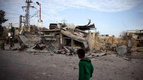 Criança caminha perto de construções destruídas por ataques na cidade de Douma; ONU pediu cessar-fogo para ajuda humanitária