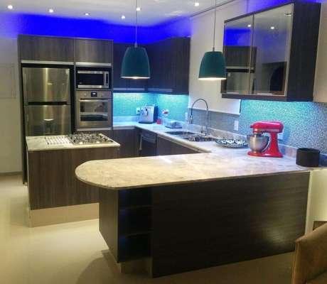 4. A cozinha planejada com ilha é uma excelente opção para ambientes pequenos