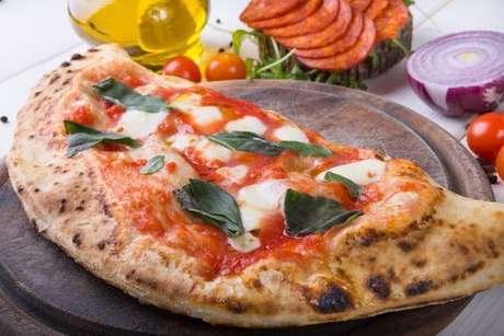Calzone decorado com molho de tomate, manjericão e pedaços de queijo
