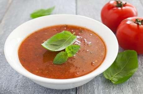 Tigela com sopa de tomate e folhas de manjericão