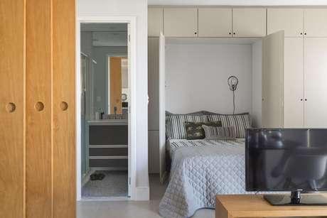 30. Guarda-roupas que vai até o teto, utilizando todo o espaço vertical disponível. Projeto de AhSim