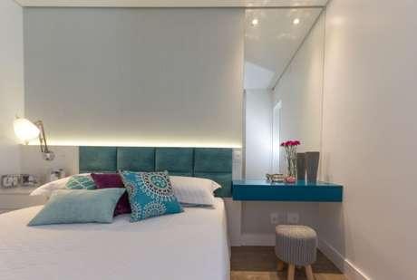 4. Quarto planejado de casal com luminária ao lado da cama e luz atrás da cabeceira. Projeto de Elen Saravalli