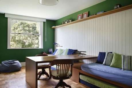 44. Aqui, o quarto de solteiro é compartilhado e a escrivaninha divide os espaços. Projeto de Migs Arquitetura