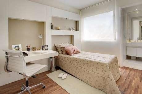 39. Quarto planejado de solteiro com móvel planejado que é escrivaninha, cabeceira e nicho. Projeto de Sesso e Dalanezi