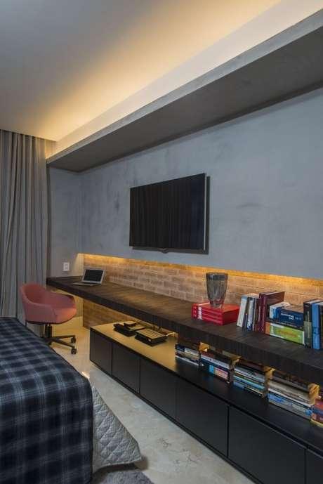 40. Os tijolinhos e a parede de cimento queimado dão ao quarto uma aparência moderna e a prateleira baixa longa é muito interessante, pois também pode ser usada como escrivaninha. Projeto de Rodrigo Maia