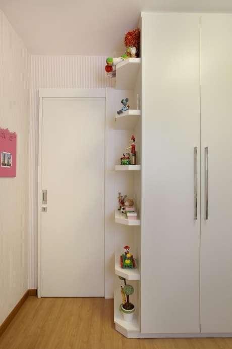 66. Quarto planejado infantil com prateleiras ao lado do armário. Projeto de Cyntia Sabat