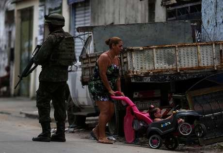 Mulher passa com criança ao lado de soldado do Exército na Vila Kennedy