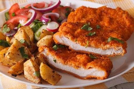 Schnitzel servido com batatas fritas e salada