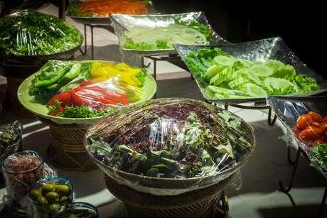 Saladas em recipientes cobertos com plástico-filme