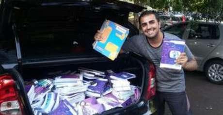 Vinícius de Andrade com material didático doado para o projeto