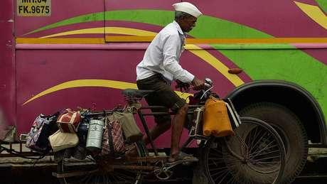 Os dabbawalas, entregadores de quentinhas, levam marmitas quentes onde quer que seja em Mumbai | Foto: AFP