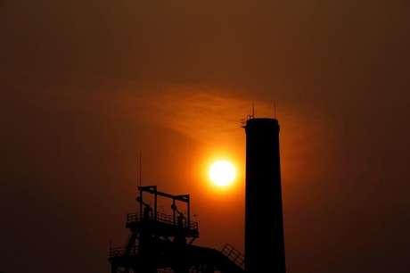Por do sol atrás de chaminé de usina de aço em Tangshan 18/02/2014 REUTERS/Petar Kujundzic
