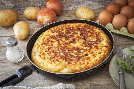 Tortilla com batatas, ovos e cebolas em volta