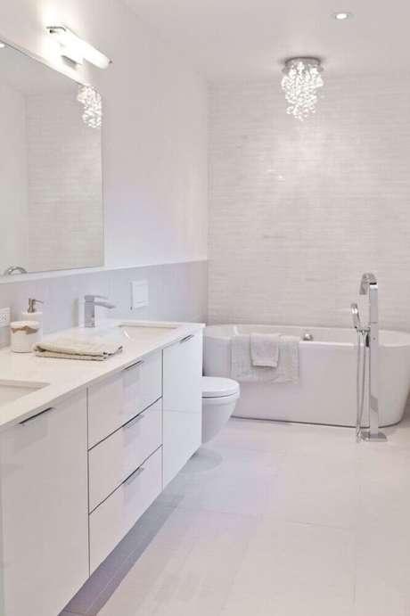 40. Banheiro todo branco com banheira e pequena luminária sofisticada