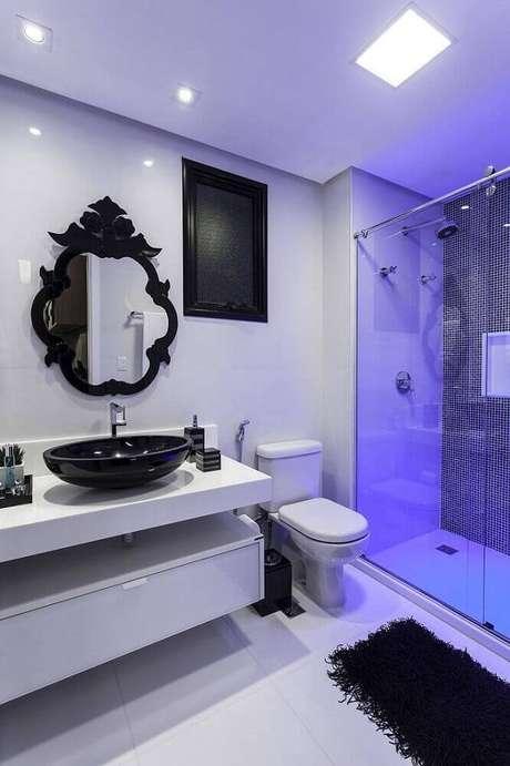 7. Esse banheiro branco é um modelo de banheiro com cerâmica preta e branca que recebeu detalhes modernos e clássicos como o espelho provençal e a bancada com linhas simples.