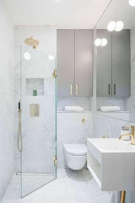 6. Decoração de banheiro branco com detalhes em dourado.