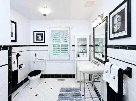 11. Banheiro preto e branco com quadros e espelho.