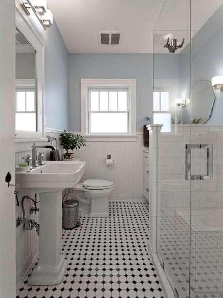34. Modelo de banheiro branco com detalhes pretos no piso.