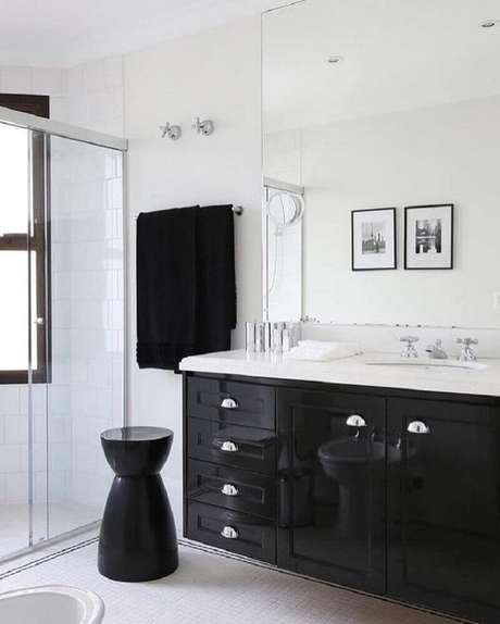 21. Esse banheiro preto e branco priorizou deixar os pretos nos detalhes como o gabinete
