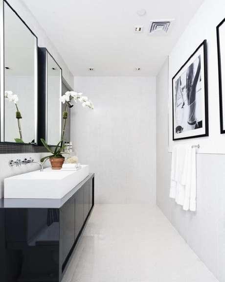 58. Banheiro preto e branco minimalista com gabinete preto e quadros na parede