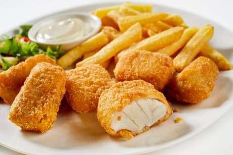 Pedaços de peixe empanados e fritos servidos com molho e batatas fritas